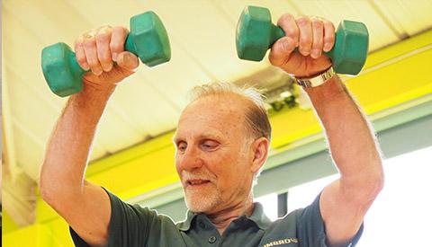 older man lifting dumbells at ymca gym