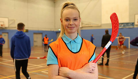 girl in ymca sports hall with hockey stick